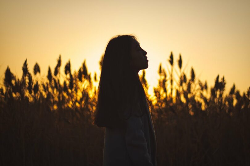 Image of a woman at sunset being a loner