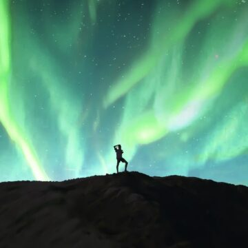 Image of a solitary person under aurora borealis being a loner