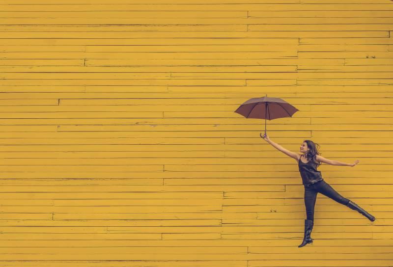 Image of an extroverted introvert woman with an umbrella dancing