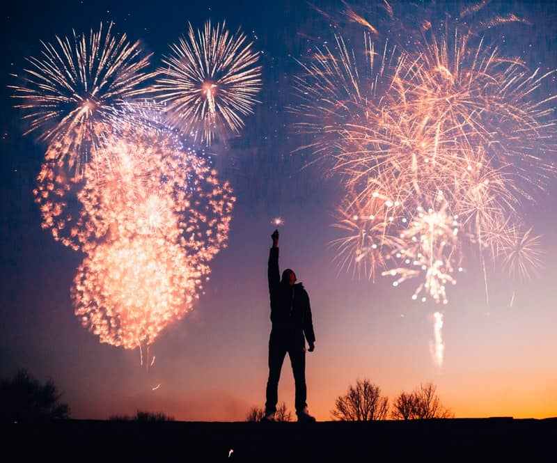 Image of an intense person standing under fireworks