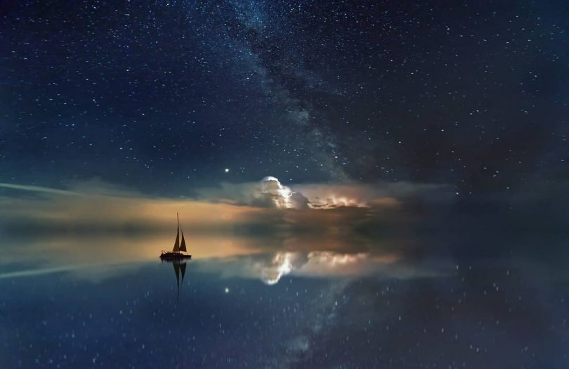 Image of a boat on the water under the stars