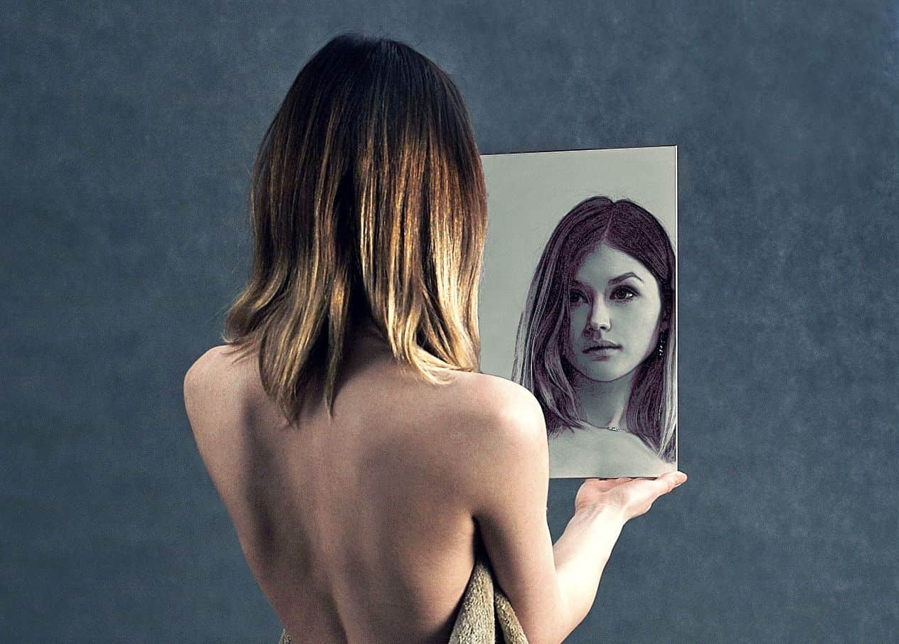 Image of a woman looking in the mirror being self-aware