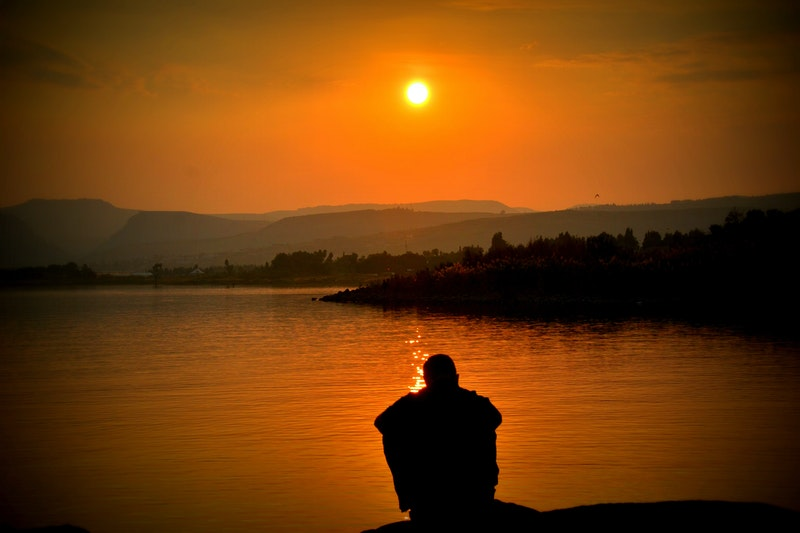 Image of a man sitting by the ocean at sunset