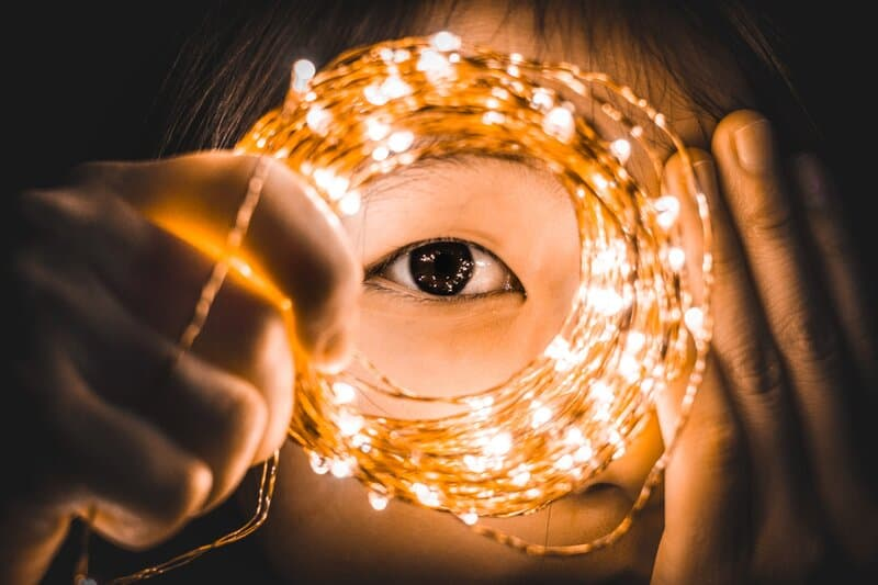 Image of a girl holding fairy lights to her eye