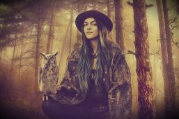 Image of an old soul woman in a forest holding an owl