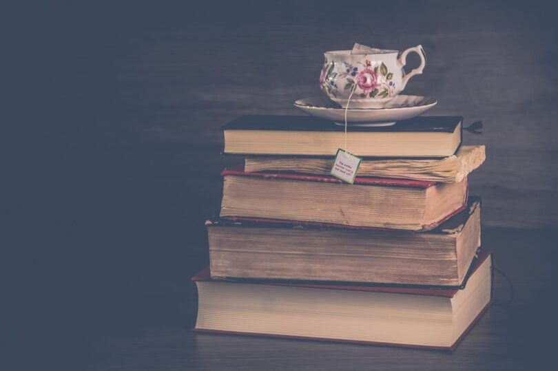 Image of old books and a teapot in a rustic living setting