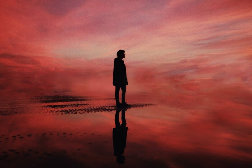 Image of a lonely person in a red landscape symbolic of the black sheep of the family