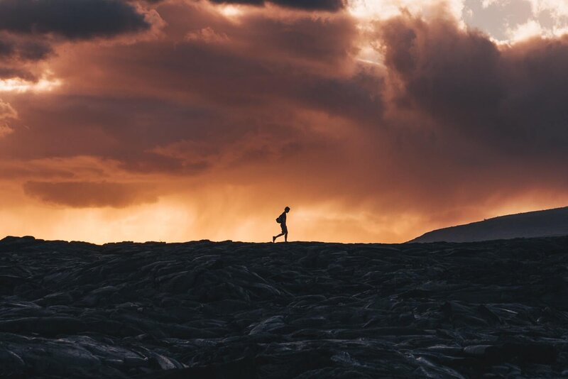 Image of a solitary person walking on a volcanic landscape