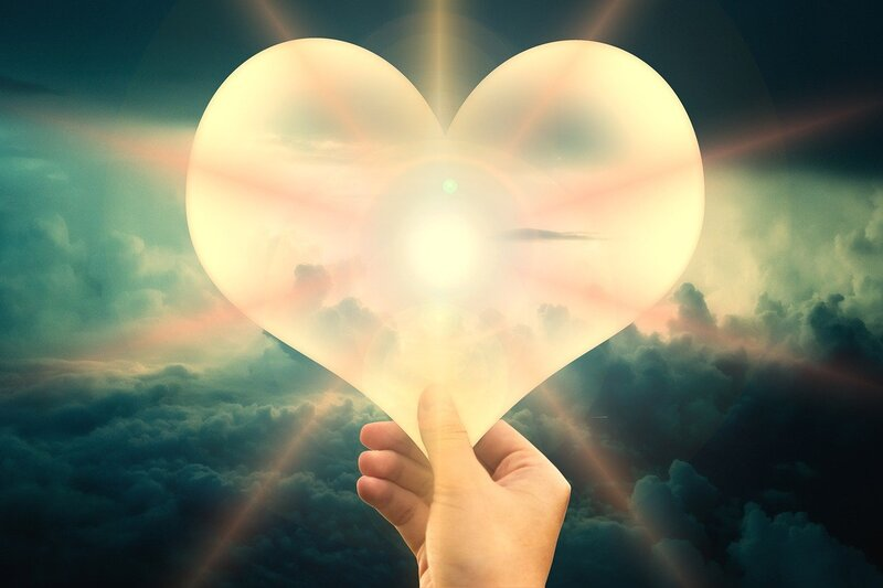 Image of a person holding a light-filled heart