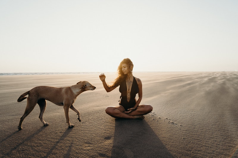 Image of a woman in the desert and her dog