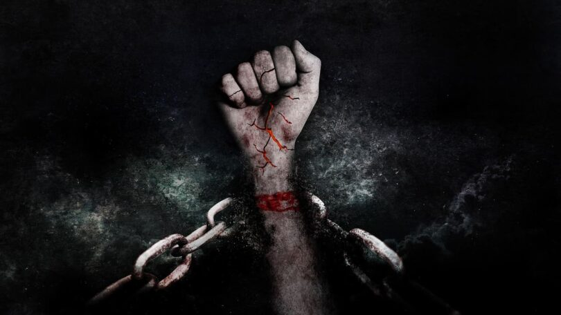 Image of a strong and resilient hand breaking through chains of adversity