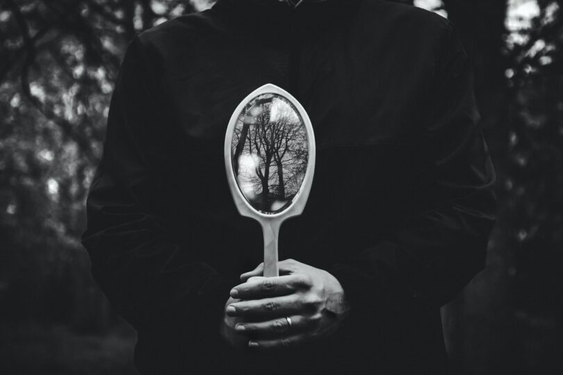 Image of a man holding up a mirror