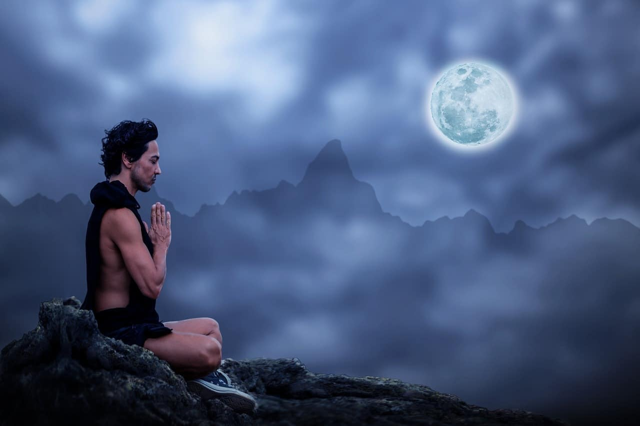 Image of a spiritual outsider man meditating under the moon