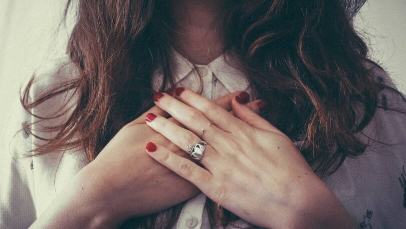 Image of a woman with hands over her heart feeling self-love