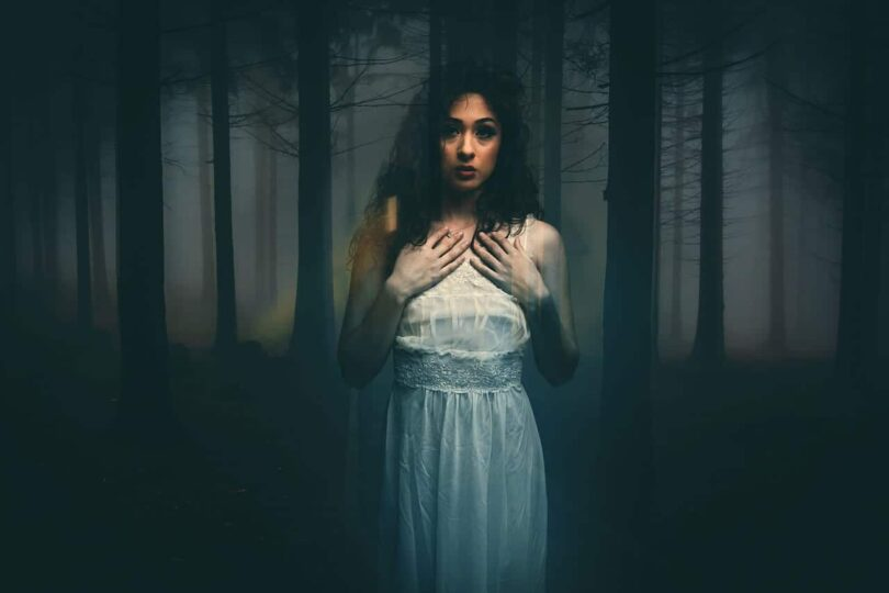 Image of a ghostly woman in a dark forest experiencing soul loss