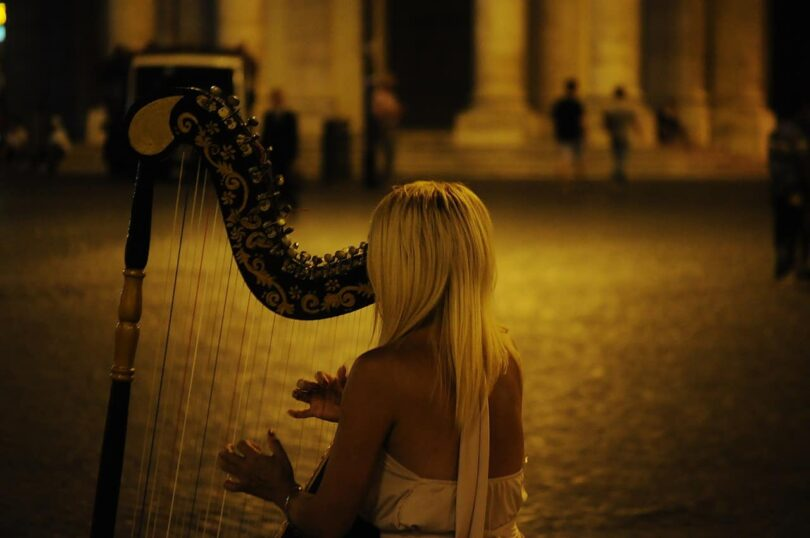 Image of a woman playing a harp doing sound healing therapy