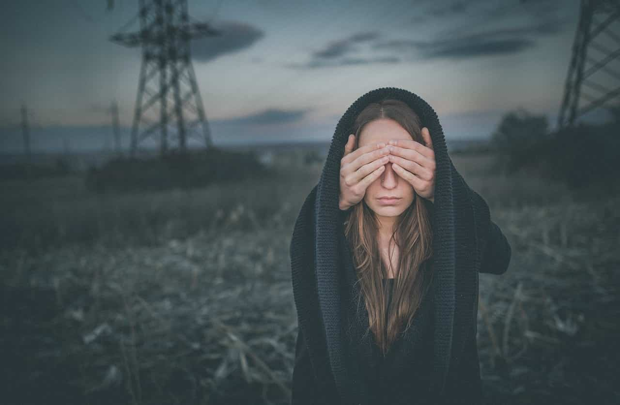 Image of a woman covering eyes having unwanted thoughts