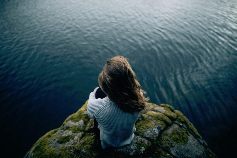 Image of a woman sitting on a cliff overlooking water contemplating freedom