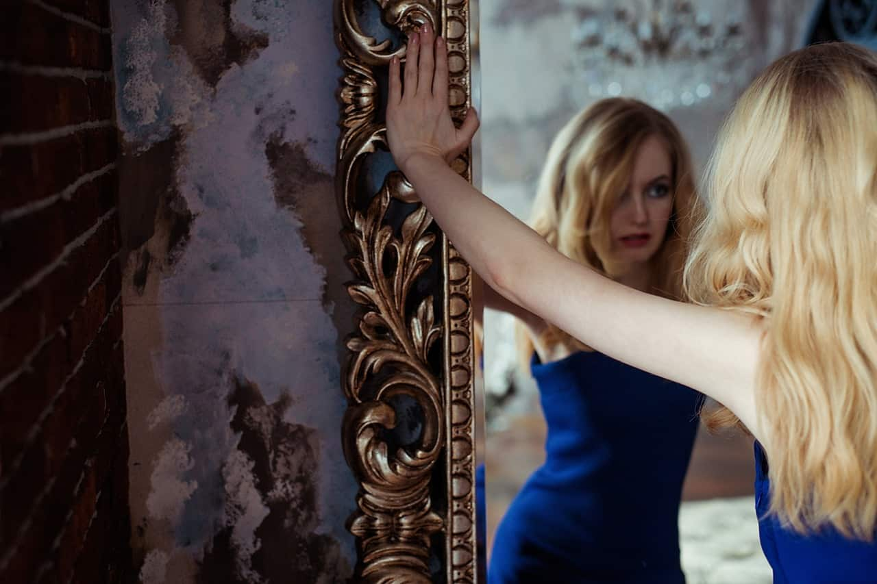 Image of a woman staring into a mirror working through her spiritual bypassing issues