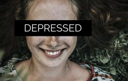 Image of a woman in a field suffering from smiling depression