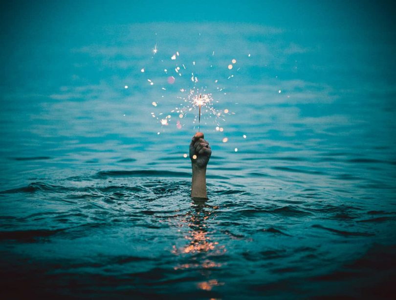 Image of a man in the water holding a sparkler symbolic of inner peace