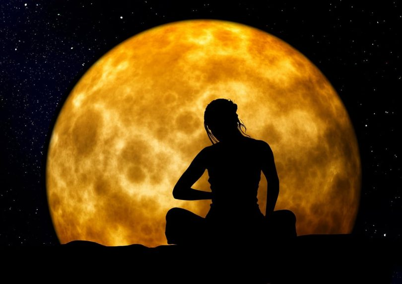 Image of a woman meditating with the moon