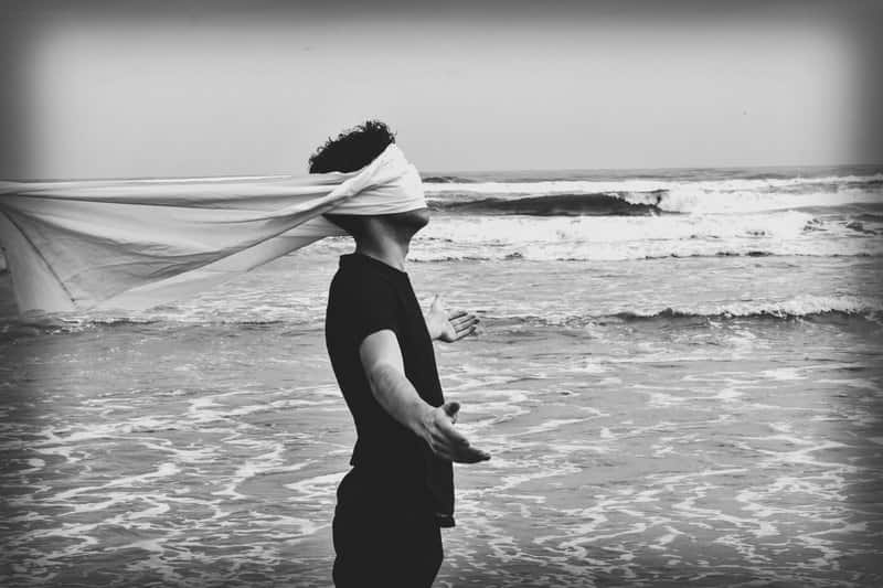image of a man with a blindfold on next to the ocean