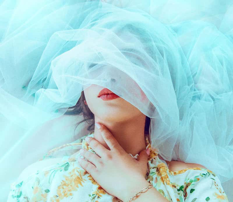 Image of a woman suffocating under a white veil