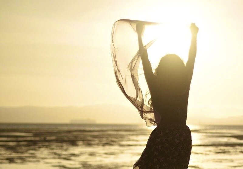 Image of a happy woman in the sunshine free from toxic core beliefs