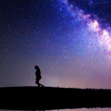 Image of an awakening soul walking underneath the stars