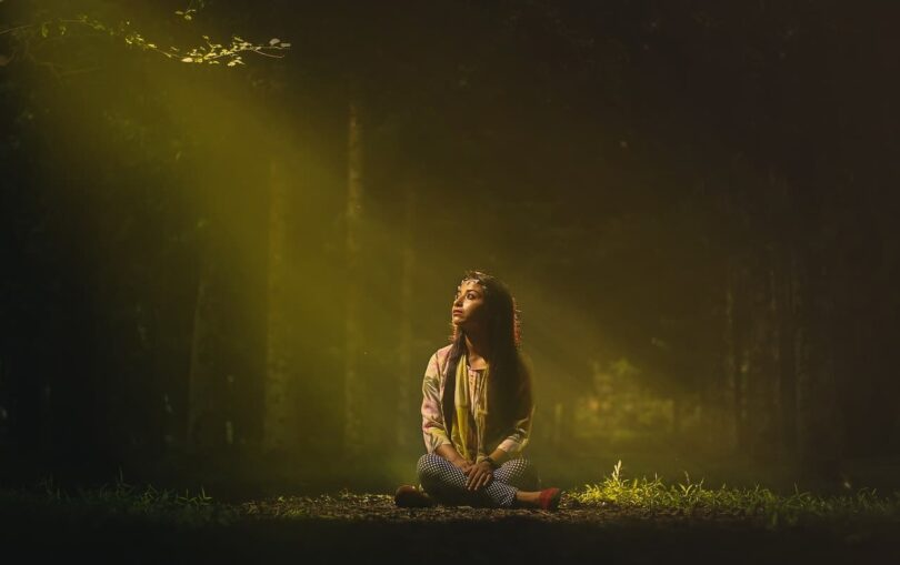 Image of a woman grounding herself in a forest