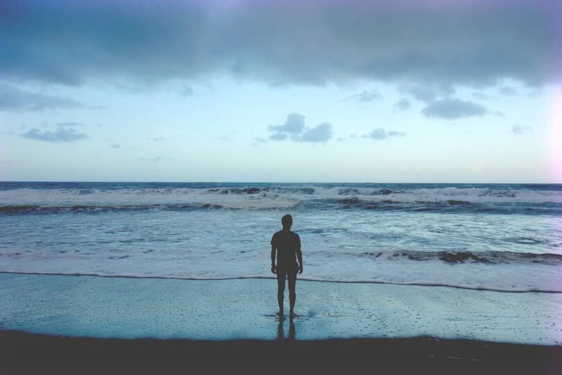 Image of a sad sensitive person standing on the beach