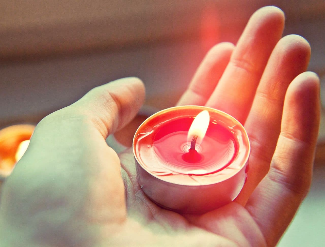 Image of a woman holding a candle doing a ritual