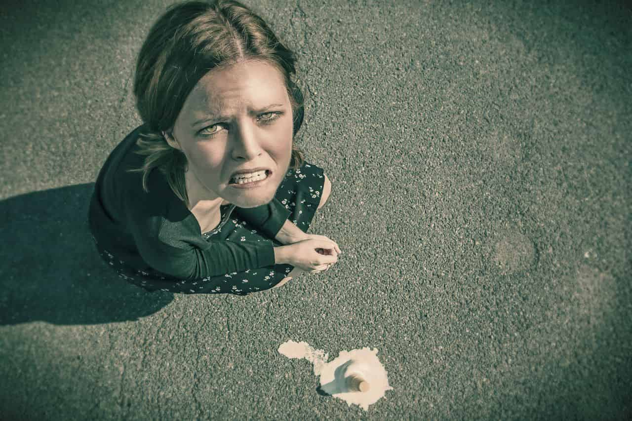 Image of an unhappy woman who dropped her icecream