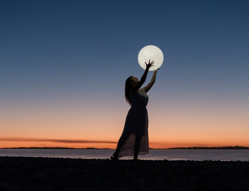 Image of a woman holding up the moon symbolic of wanting to change the world