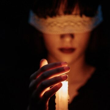 Image of a person holding a candle symbolic of being a lightworker