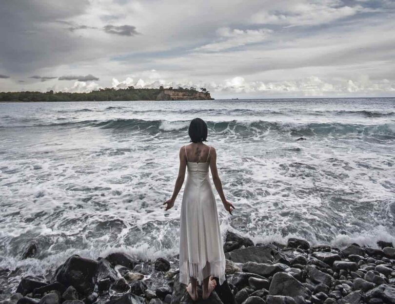 Image of a sad and lonely woman standing on the beach