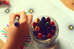 Image of an adult coloring in a page with crayons