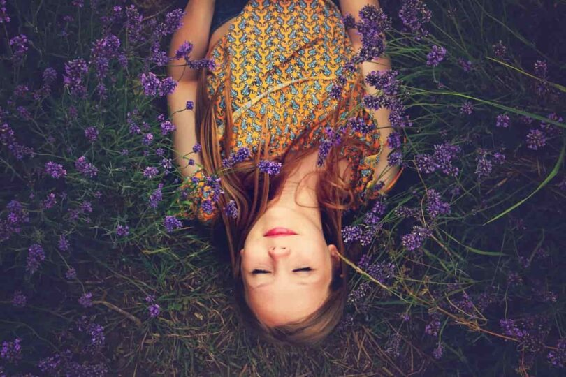 Image of a serene girl lying in a field of flowers symbolic of learning how to love yourself
