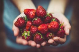 Image of a woman holding strawberries practicing intuitive eating