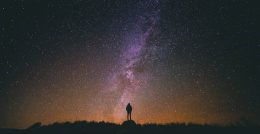 Image of a woman staring at the cosmic sky contemplating all she can't see