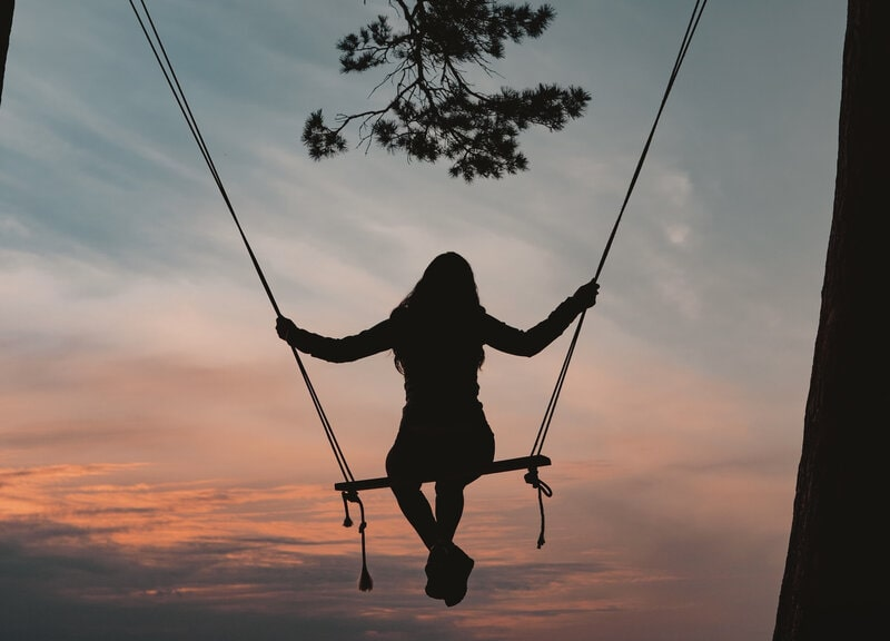 Image of a woman on a swing at sunset