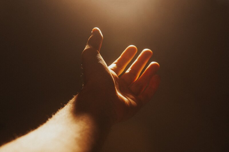 Image of a person reaching out to the light