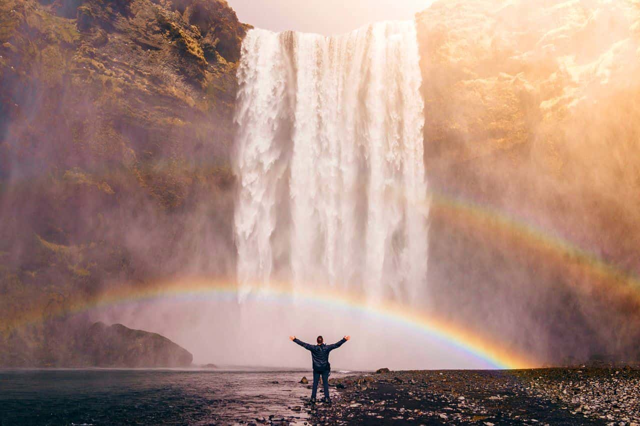 Image of a man standing under a rainbow experiencing empowerment