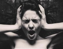 Image of an angry woman holding her head in rage