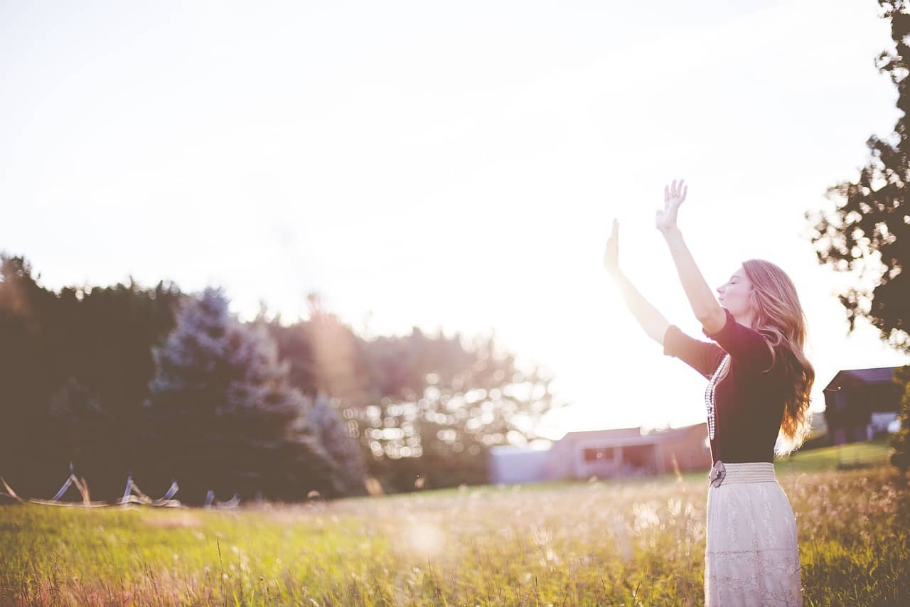 Image of a happy woman in the sunlight who feels whole