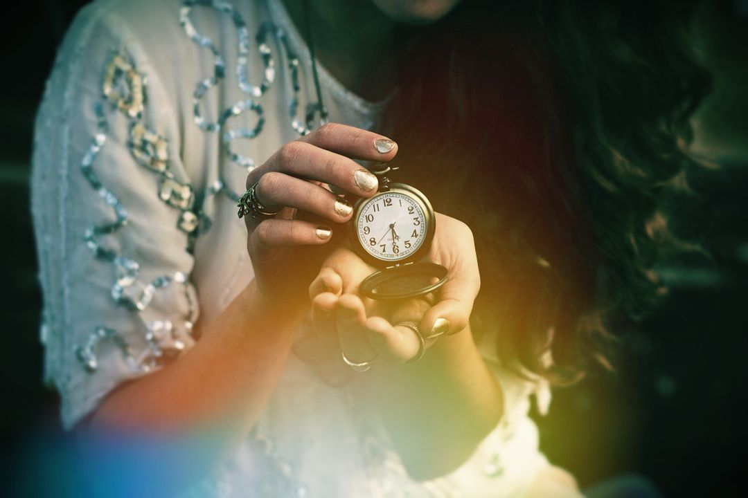 Image of a woman holding a pocket watch symbolic of karma and destiny