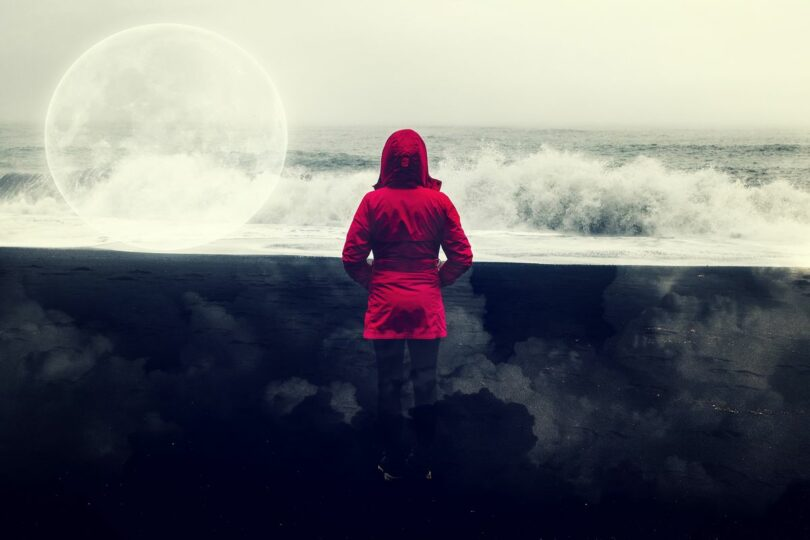 Image of a woman in red at the beach symbolic of the period cycle