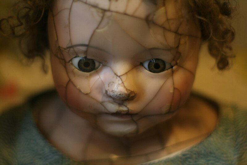 Image of a creepy doll face that represents childhood trauma