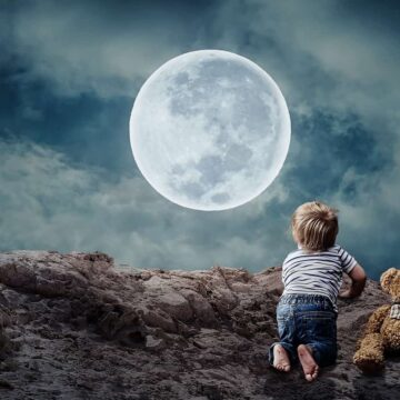 Image of a little boy looking at the moon symbolic of inner child work